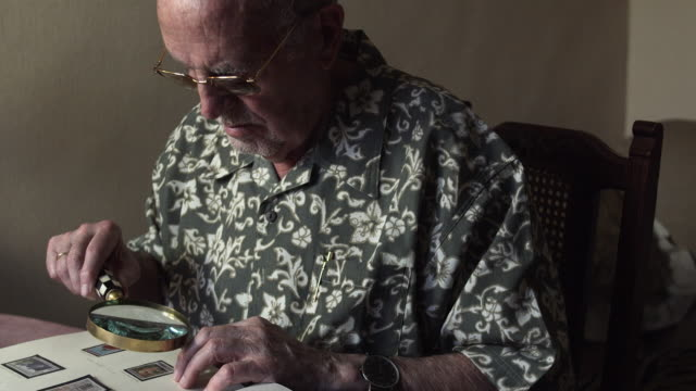 vidéos et rushes de ms pan td senior man is looking at an album of old stamps / bilbao, vizcaya, spain. - collection