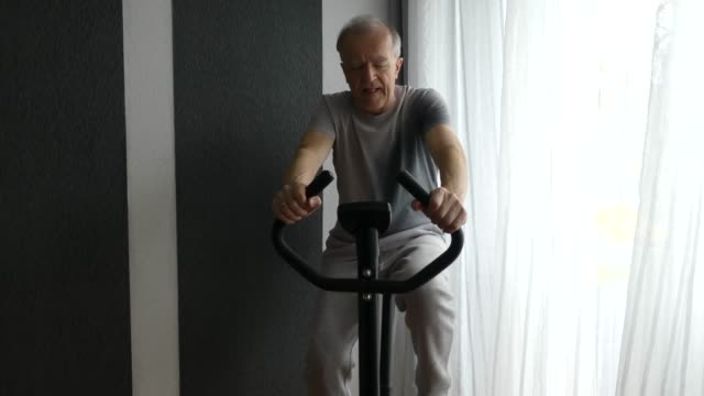 senior man is riding an exercise bike. - exercise bike stock videos & royalty-free footage
