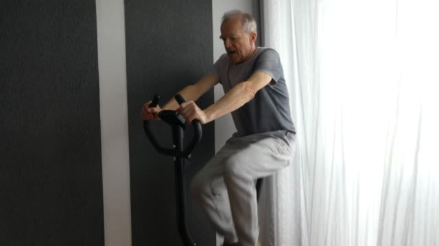 senior man is riding an exercise bike. - exercise bike stock videos & royalty-free footage