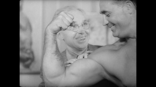 vídeos de stock e filmes b-roll de senior man is very impressed by charles atlas' bicep curl touches his arm - body building