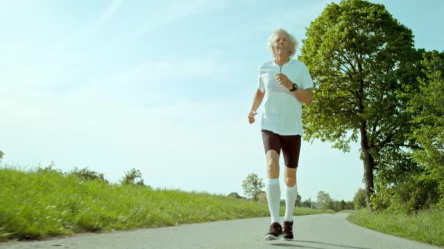 SLO MO TS Senior man jogging in nature