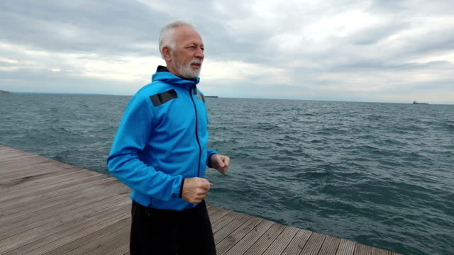 senior man jogging next to the sea - 50 54 years stock videos & royalty-free footage