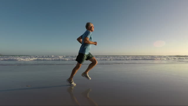 vídeos de stock e filmes b-roll de senior man jogging on a beautiful beach at sunset - one senior man only