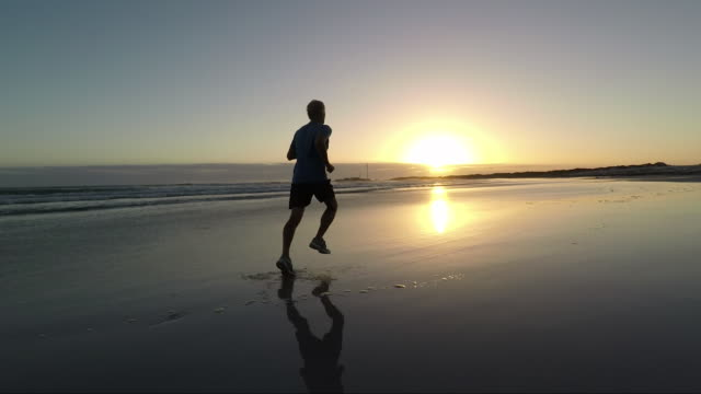 senior man jogging on a beautiful beach at sunset - only men stock videos & royalty-free footage