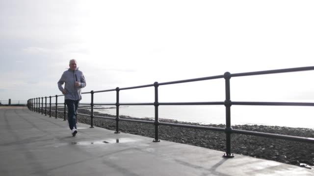 vídeos de stock e filmes b-roll de senior man jogging outdoors - 70 anos