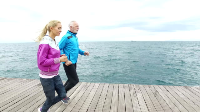 senior man jogging with young woman next to the sea - the ageing process stock videos & royalty-free footage