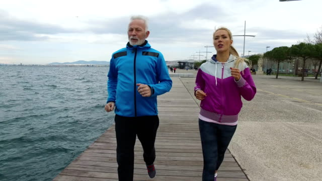 Senior man Jogging with young woman next to the sea
