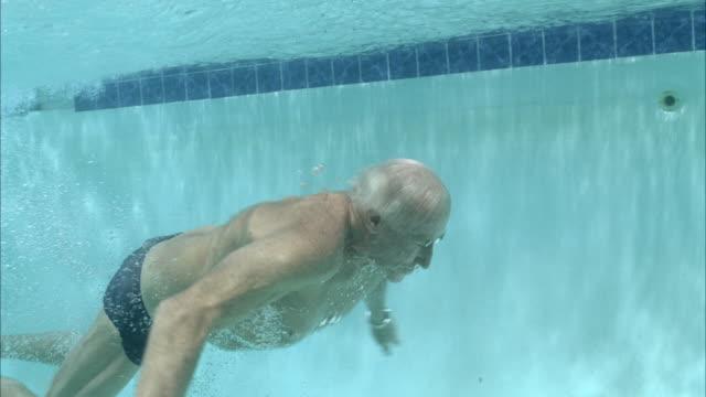 SLO MO MS Senior man jumping into swimming pool / Aspen, Colorado, USA