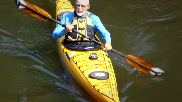 vidéos et rushes de senior homme en kayak dans la nature-ha - pagayer