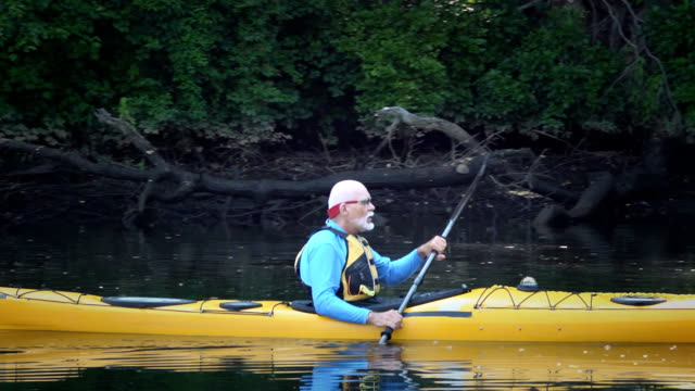 senior man kayaking in nature - ls - active seniors stock videos & royalty-free footage