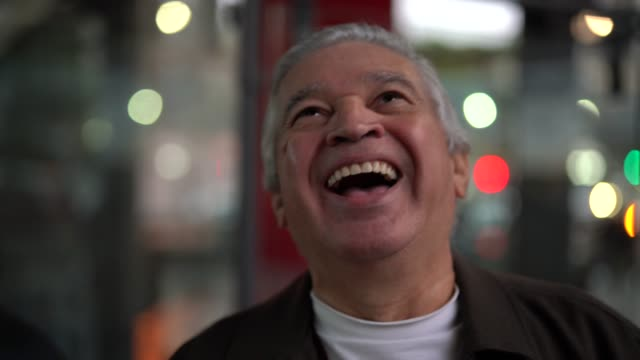 シニア男が笑って街の夜 - 表す点の映像素材/bロール