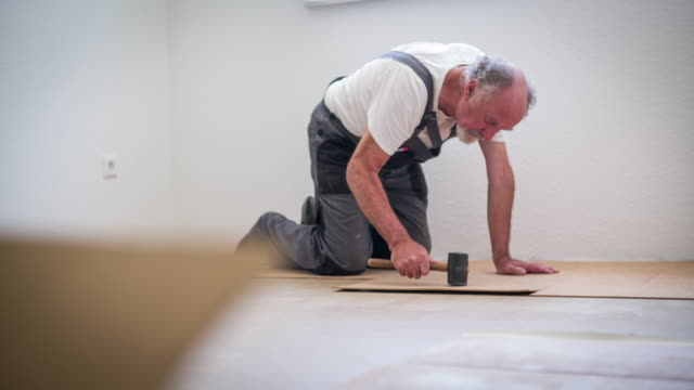 senior man laying cork flooring in his house - hammer stock videos & royalty-free footage