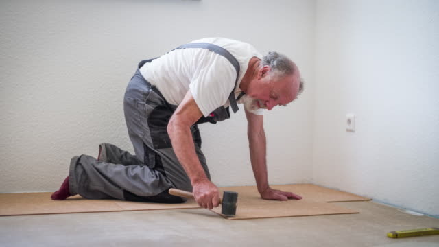 senior man laying cork flooring in his house - cork material stock videos & royalty-free footage
