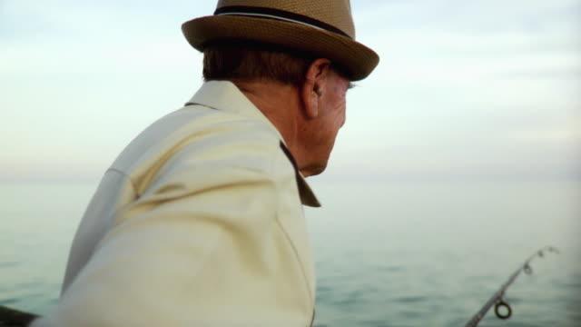 MS Senior man leaning against railings holding fishing pole / Jacksonville Beach, Florida, USA