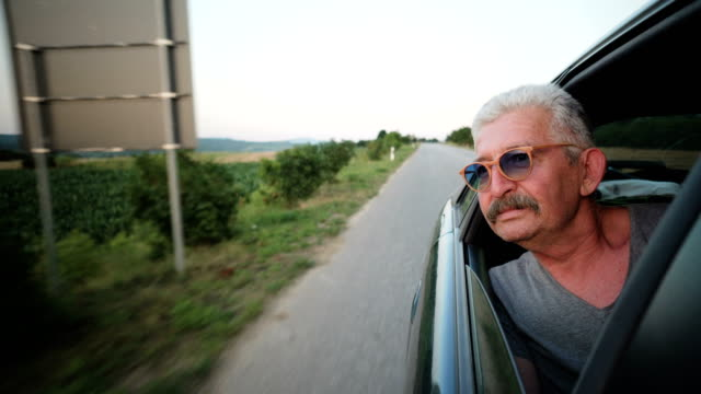Senior man leaning out of a car window