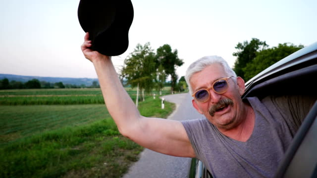 senior man leaning out of a car window - etnia video stock e b–roll