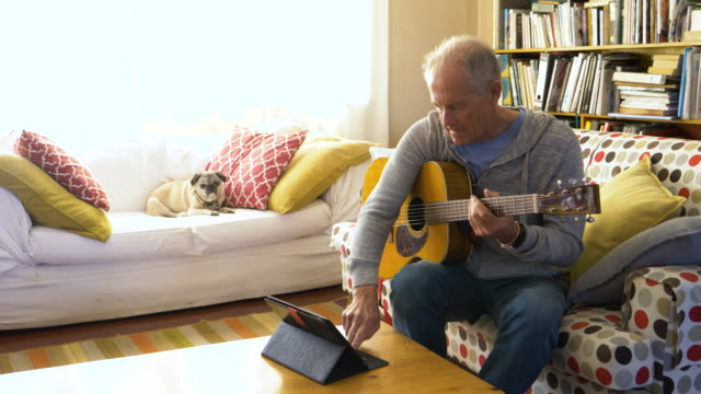 senior man learning guitar by watching online tutorial - learning stock videos & royalty-free footage