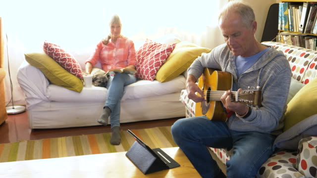 senior man learning guitar by watching online tutorial - tutorial stock videos and b-roll footage