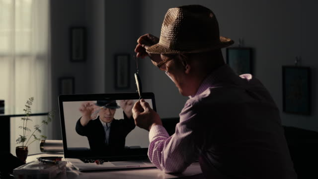 senior man learning lure fishing online at home as a hobby - hobbies点の映像素材/bロール