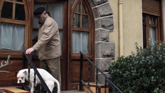 vídeos de stock e filmes b-roll de ms pan senior man leaving home with three boxer dogs / bilbao, vizcaya, spain. - desembarcar