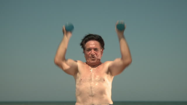 vídeos y material grabado en eventos de stock de ms tu senior man lifting dumbbells on beach, jacksonville, florida, usa - 80 89 años