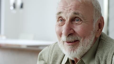 vídeos y material grabado en eventos de stock de senior hombre escucha asesor en sala de estar - viejo
