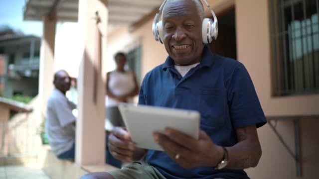 senior man listening music on digital tablet at home - singing stock videos & royalty-free footage