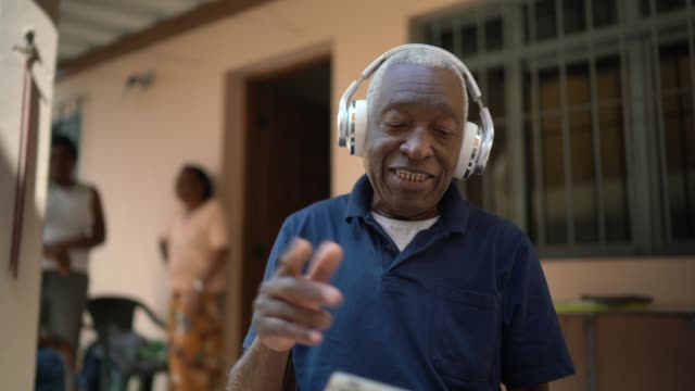 senior man listening music on digital tablet at home - headphones stock videos & royalty-free footage