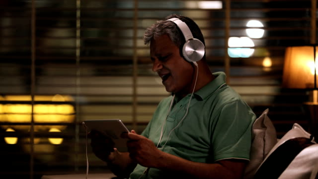 Senior man listening music on headphone, Delhi, India