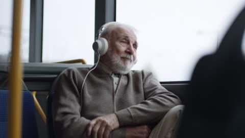 senior man listening music on headphones in bus - bus stock videos & royalty-free footage