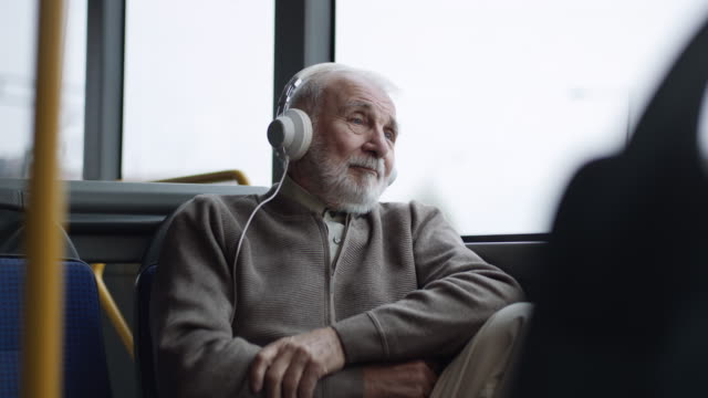 senior man listening music on headphones in bus - headphones stock videos & royalty-free footage
