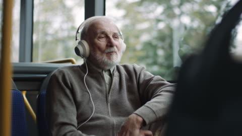 vídeos y material grabado en eventos de stock de hombre mayor escuchando música en auriculares en autobús - escuchar