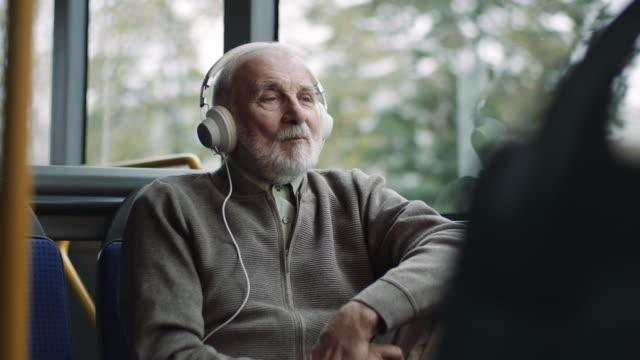 vídeos de stock e filmes b-roll de senior man listening music on headphones in bus - autocarro