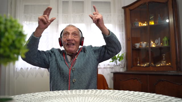 senior man listening  music on headphones - tuff attityd bildbanksvideor och videomaterial från bakom kulisserna