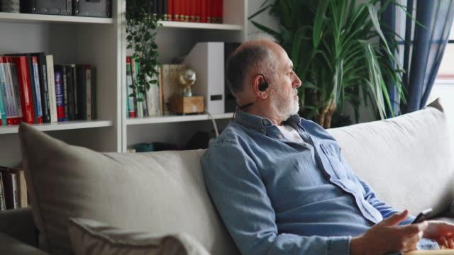 vidéos et rushes de homme aîné écoutant le podcast à la maison - one young man only