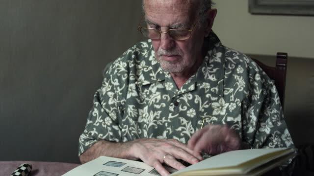 vidéos et rushes de ms tu td senior man looking at album of old stamps through magnifying glass / bilbao, vizcaya, spain. - collection