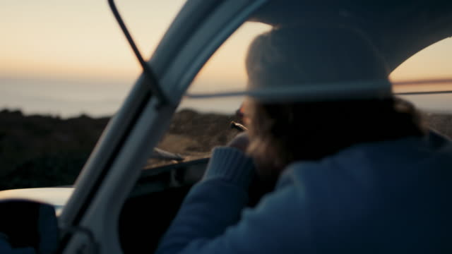 vídeos de stock e filmes b-roll de senior man looking at ocean and sunset from his car - admirar a vista