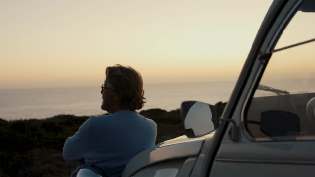 senior man looking at ocean at dusk - pensionierung stock-videos und b-roll-filmmaterial