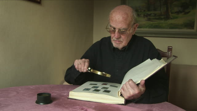 MS Senior man looking at stamp collection through magnifying glass, Bilbao, Spain