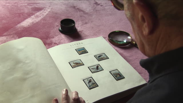 cu senior man looking at stamp collection through magnifying glass, bilbao, spain - briefmarke stock-videos und b-roll-filmmaterial