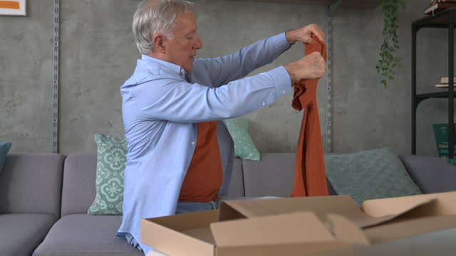 senior man looking at t-shirt that he bought online while sitting on sofa at home - t shirt stock videos & royalty-free footage