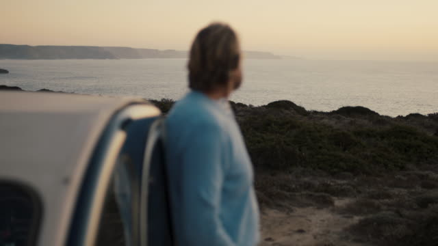 vídeos de stock e filmes b-roll de senior man looking out on ocean in evening - horizonte
