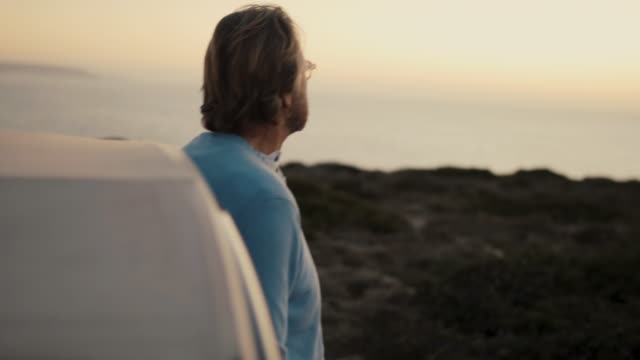 vidéos et rushes de senior man looking out on ocean in evening - personne sereine