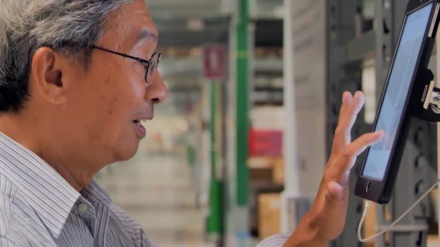 senior mann nach bestellen details auf einem tablet, wie er einkaufen. senior mann mit touchscreen-gerät für online-shopping. technologie,menschen,online-shopping-konzept. haus waren einkaufen - distribution warehouse stock-videos und b-roll-filmmaterial