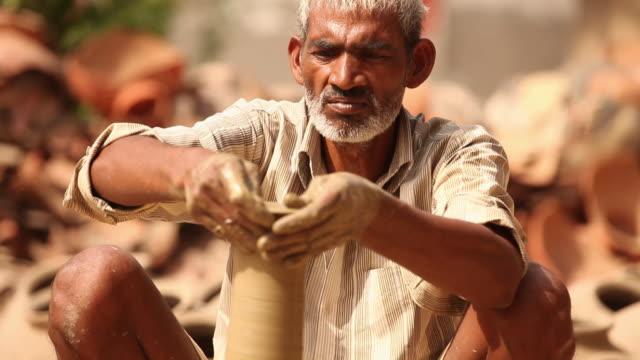 vídeos de stock e filmes b-roll de senior man making a earthen pot on a pottery wheel, faridabad, haryana, india - só homens maduros