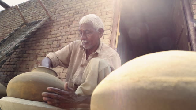 Senior man making earthen pot, Haryana, India