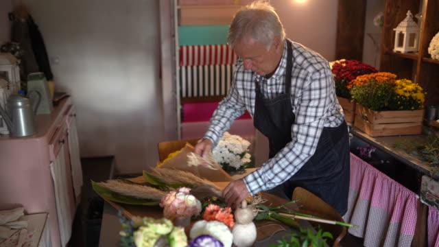 senior man making flower arrangement at flower shop - flower arrangement stock videos & royalty-free footage