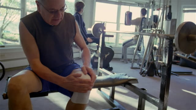 MS, senior man massaging bandaged knee, sitting in gym, USA, Pennsylvania, Solebury