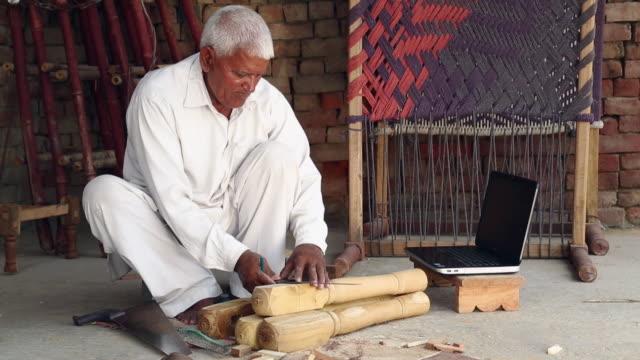 Senior man measuring wood with the help of laptop, Haryana, India