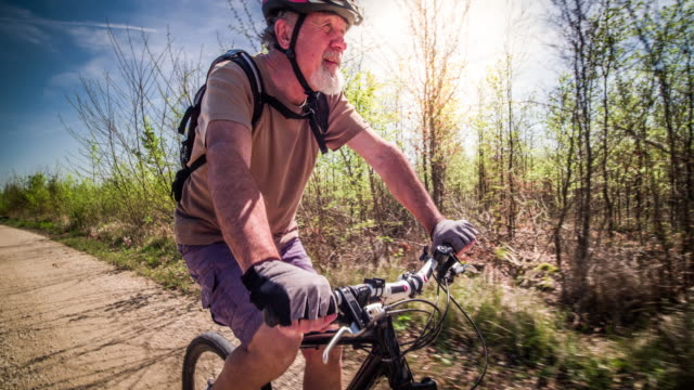senior man mountain biking - terza età video stock e b–roll